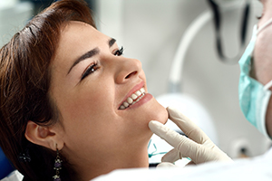 Woman smiling while dentist checks her teeth