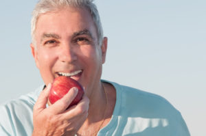 man smiling preparing to eat apple