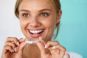 A woman holding a clear aligner and smiling.