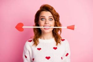 A woman wearing a white sweater with red hearts is holding an arrow with a heart at the tip between her teeth