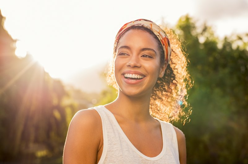 a young woman standing outside enjoying the weather and showing off her smile